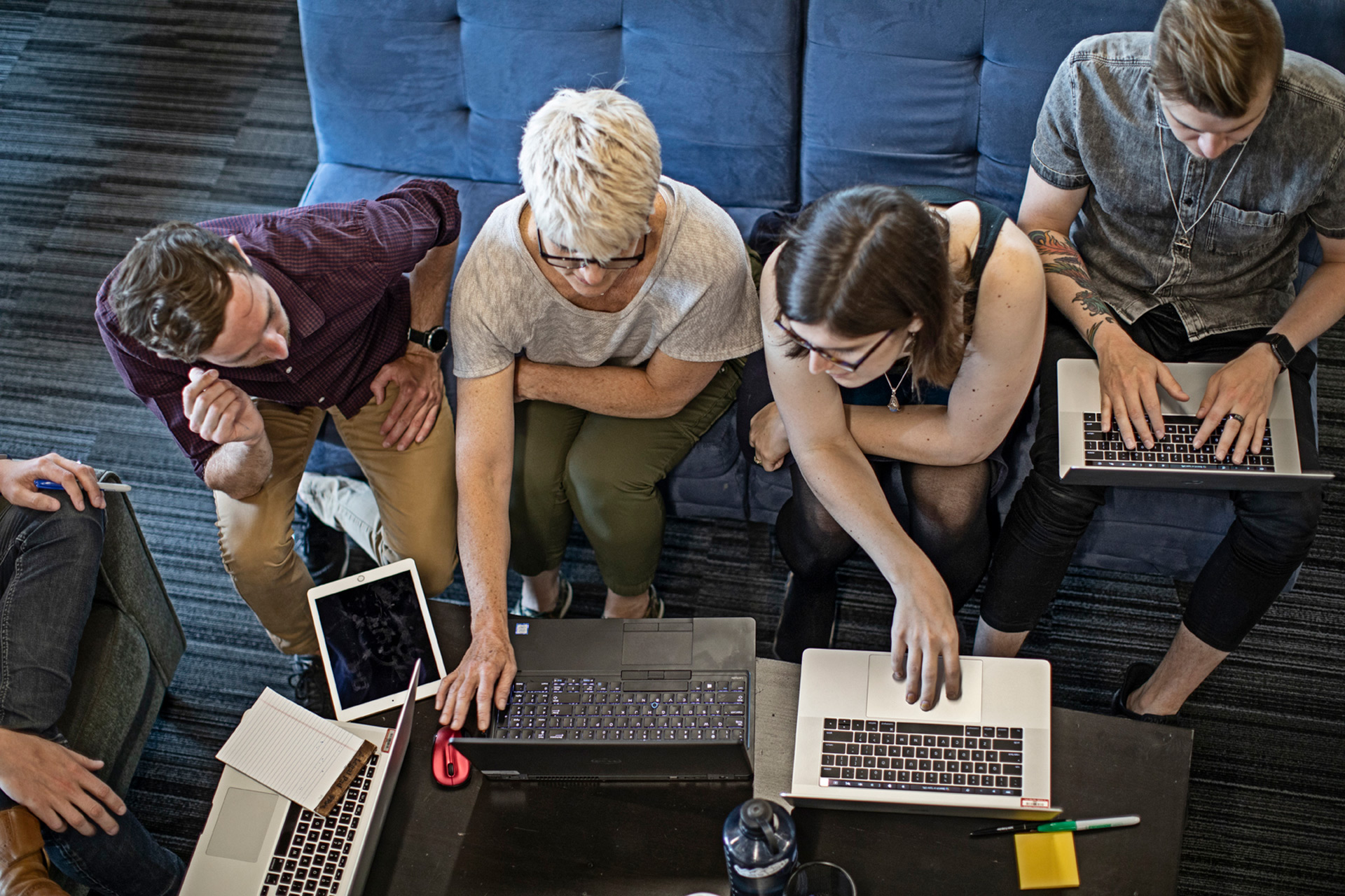 people sitting on couch looking over computers