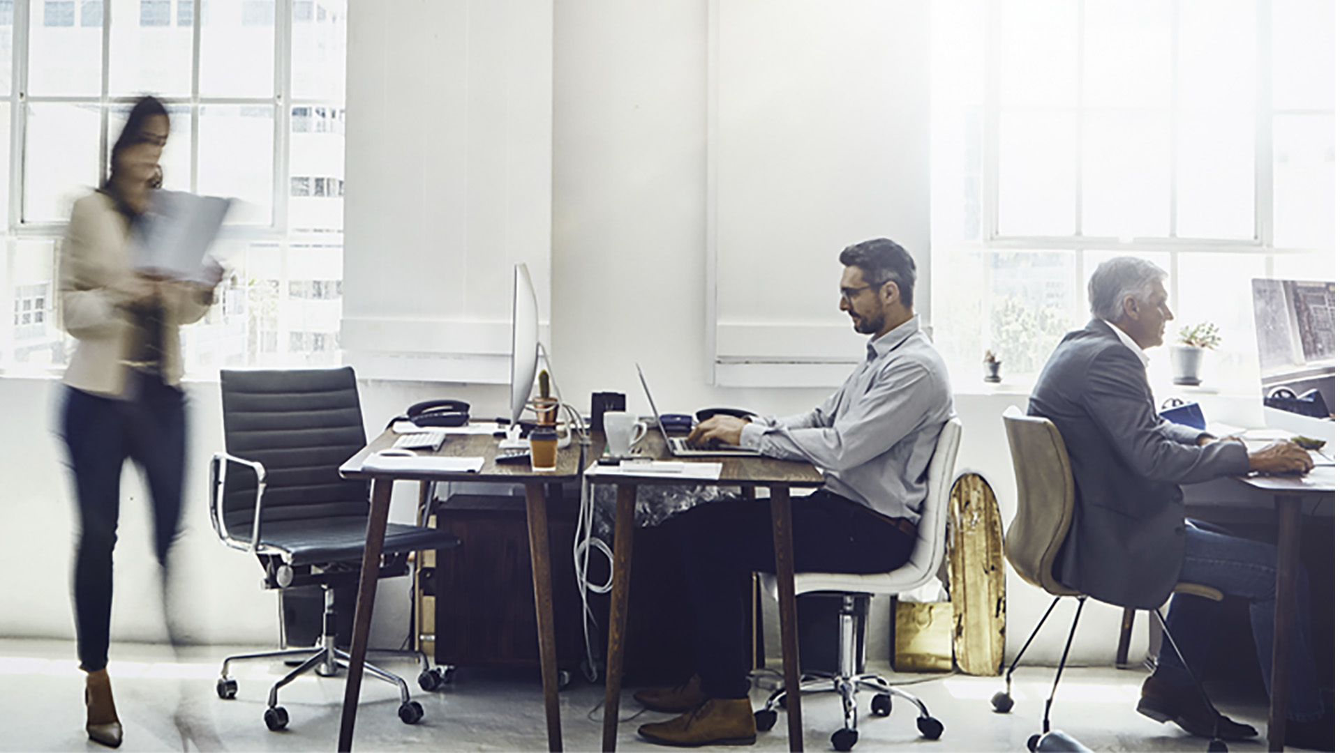 photo of three people working in modern office