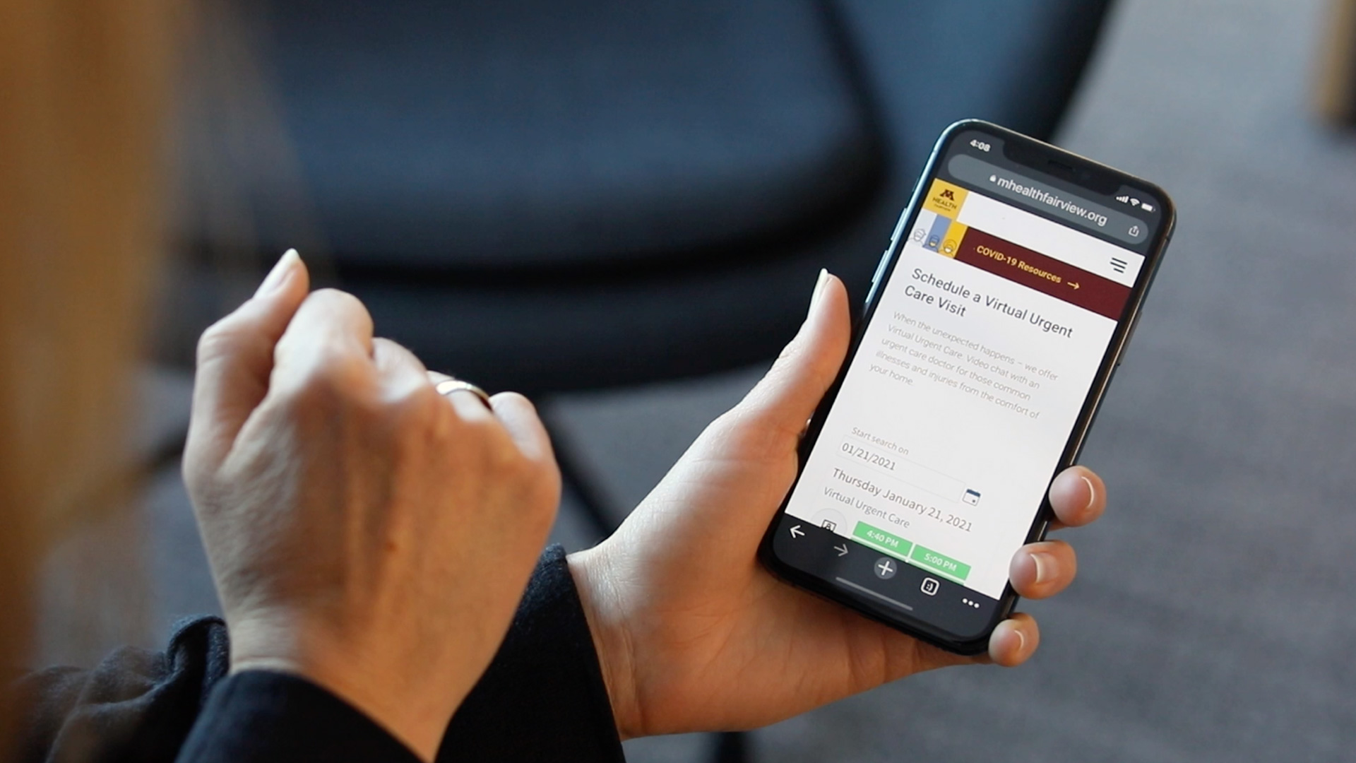 Hands holding a mobile phone and navigating M Health Fairview website