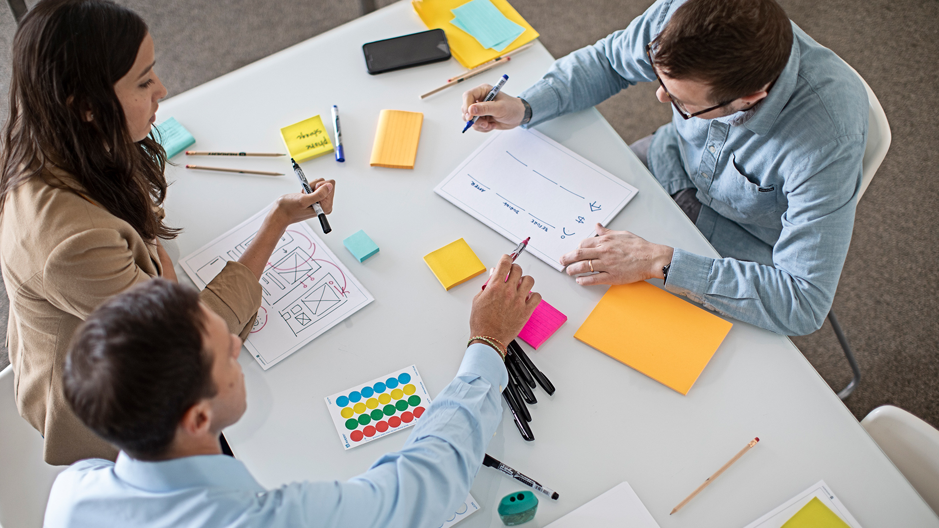 three people working at a table with sticky notes, pens and paper