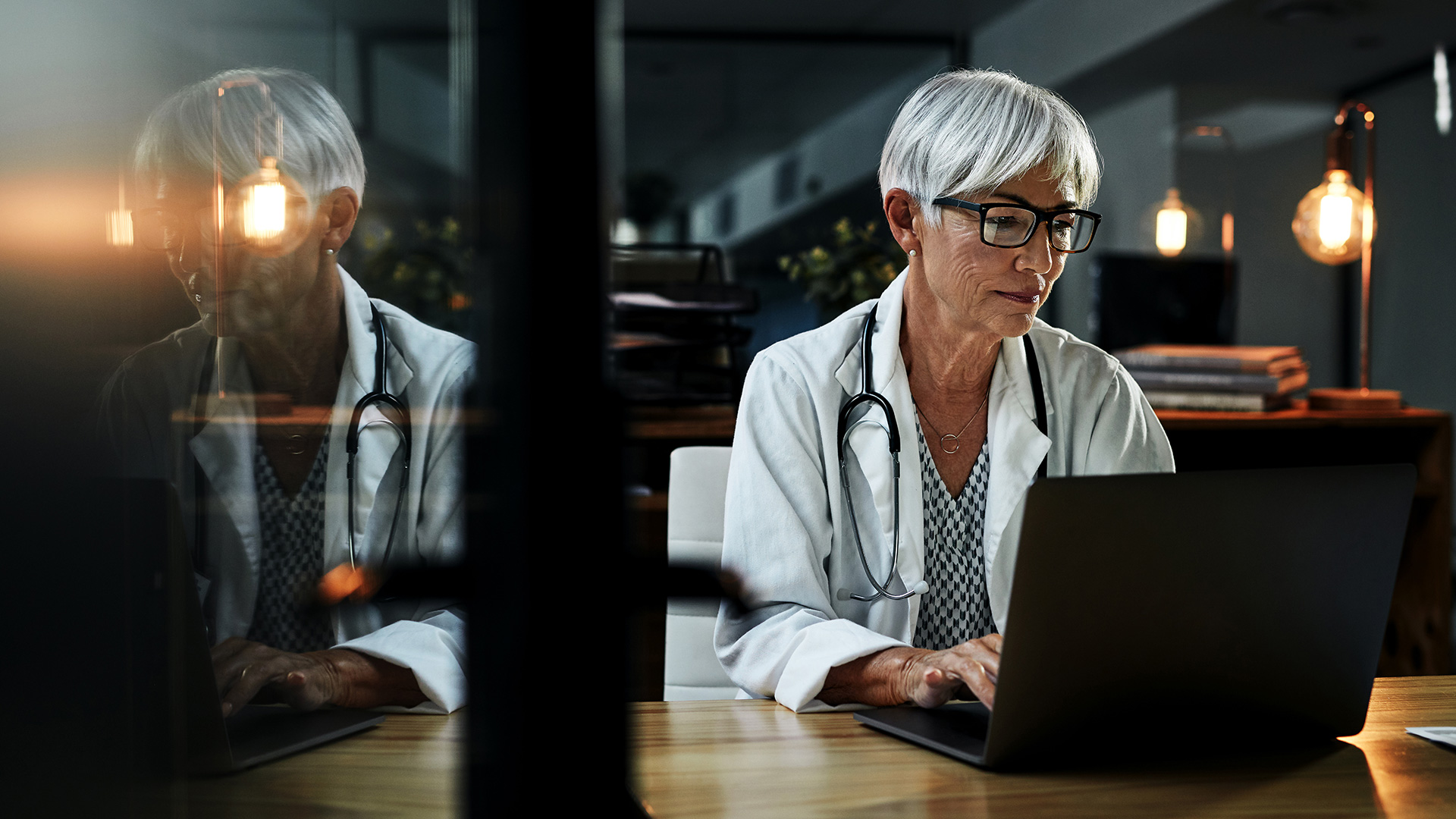 Woman doctor working on laptop at desk