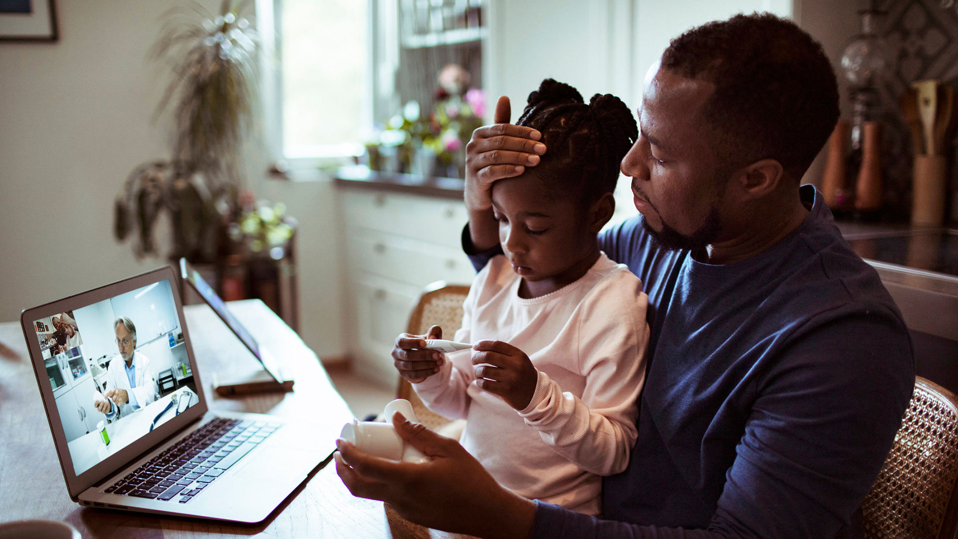 Father and daughter doing a virtual care visit with a provider on laptop