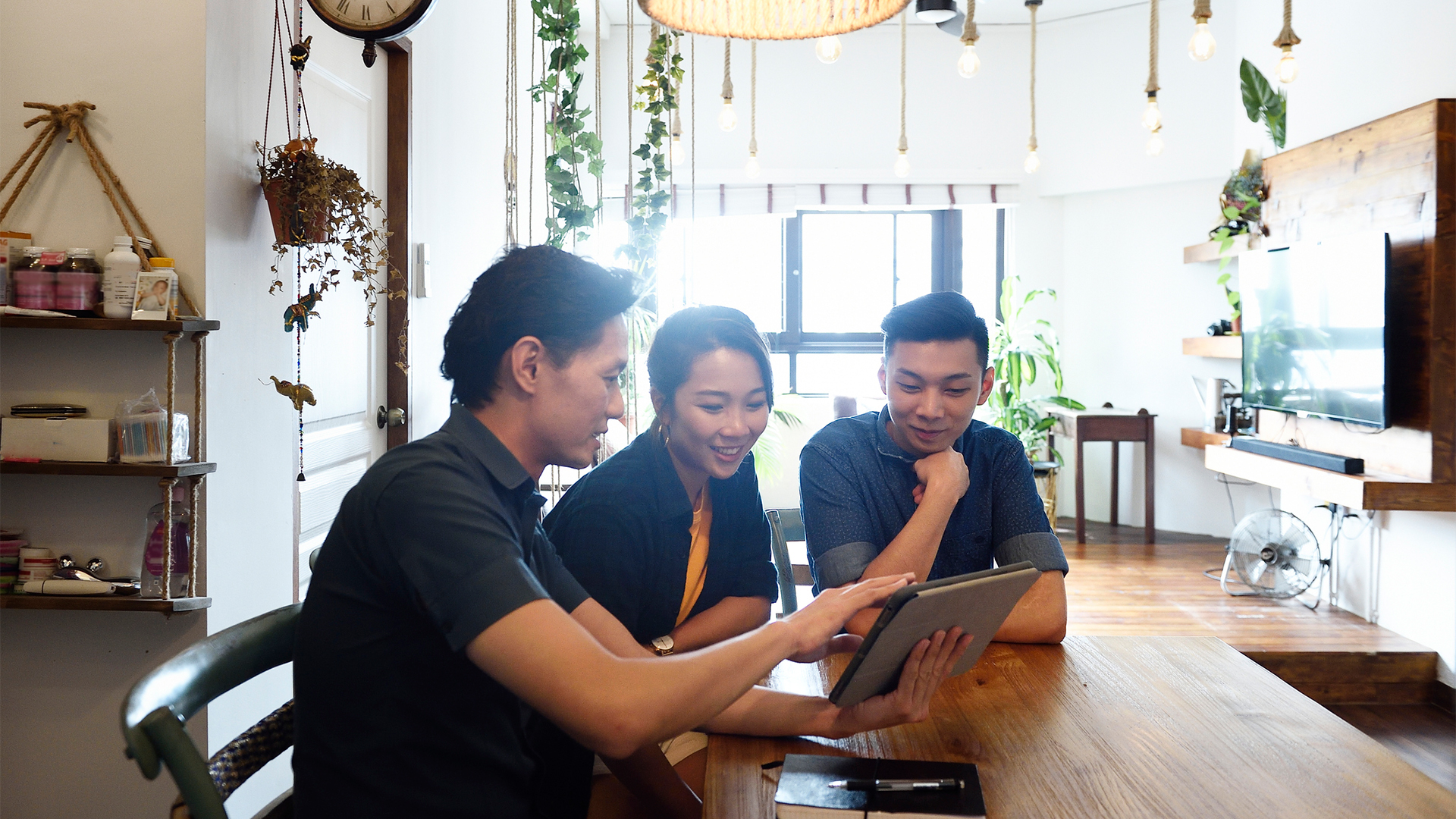 three people collaborating on a tablet